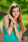 Retrato de una mujer joven en un fondo de árboles verdes — Foto de Stock