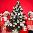 Portrait of Santa hat Christmas girls holding christmas gifts smiling happy and excited. Cute beautiful santa children on red background. — Stock Photo #37669725