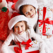 Portrait of Santa hat Christmas girls holding christmas gifts smiling happy and excited. Cute beautiful santa children on red background. — Stock Photo #37669727
