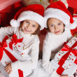 Portrait of Santa hat Christmas girls holding christmas gifts smiling happy and excited. Cute beautiful santa children on red background. — Stock Photo #37669731
