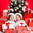 Portrait of Santa hat Christmas girls holding christmas gifts smiling happy and excited. Cute beautiful santa children on red background. — Stock Photo #37669733