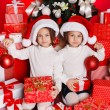 Portrait of Santa hat Christmas girls holding christmas gifts smiling happy and excited. Cute beautiful santa children on red background. — Stock Photo #37669737