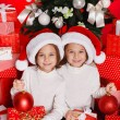 Portrait of Santa hat Christmas girls holding christmas gifts smiling happy and excited. Cute beautiful santa children on red background. — Stock Photo