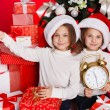 Portrait of Santa hat Christmas girls holding christmas gifts smiling happy and excited. Cute beautiful santa children on red background. — Stock Photo #37669759