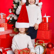 Portrait of Santa hat Christmas girls holding christmas gifts smiling happy and excited. Cute beautiful santa children on red background. — Stock Photo #37669771
