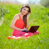 Portrait of a smart young woman lying on grass and using laptop — Stock Photo