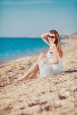 Portrait of a beautiful young woman on the beach in the sand — Stockfoto