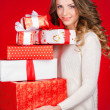 Santa girl holding christmas gift. Young happy woman in santa hat looking sideways showing Christmas present isolated on white background. Beautiful cute young santa woman. — Stock Photo #37671047