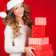 Santa girl holding christmas gift. Young happy woman in santa hat looking sideways showing Christmas present isolated on white background. Beautiful cute young santa woman. — Stock Photo #37671069