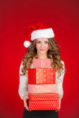 Santa girl holding christmas gift. Young happy woman in santa hat looking sideways showing Christmas present isolated on white background. Beautiful cute young santa woman. — Stock Photo