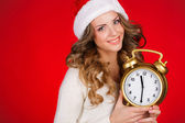 Young woman in a Santa hat on a red background, the clock 11-30 — Stock Photo
