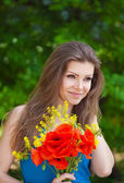 Portrait of cheerful woman outdoor with red poppy flowers in her hands — Fotografia Stock