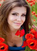 Portrait of cheerful woman outdoor with red poppy flowers in her hands — Stockfoto