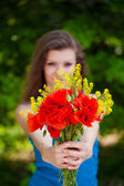 Portrait of cheerful woman outdoor with red poppy flowers in her hands — Stock Photo