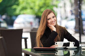 Portrait of beautiful smiling woman sitting in a cafe with laptop outdoor — Stock Photo