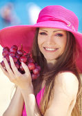 Portrait of beautiful woman with grapes in hands in summer outdoor — Stock Photo