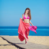 Young beautiful woman on the beach near the sea in summer — Stock Photo