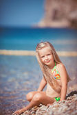 Little girl sitting on the beach near the sea — Stock Photo