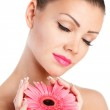 Portrait of beautiful woman with bright make up holding pink daisy in hands — Stock Photo #37852551