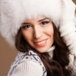 Studio portrait of a young woman in fluffy white hat and mittens — Stock Photo