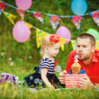 Family celebrating birthday party in green park outdoors — Stock Photo #37857533