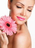 Portrait of beautiful woman with bright make up holding pink daisy in hands — Stock Photo