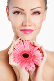 Portrait of beautiful woman with bright make up holding pink daisy in hands — Stockfoto