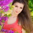 Stock Photo: Beautiful young brunette womon meadow with white flowers on warm summer day