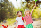 Cute happy children playing in spring filed — Stock Photo