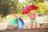 Cute little girl playing with watermelons in summer park outdoors — Stock Photo