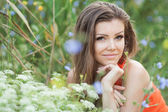 Beautiful young brunette woman on the meadow with white flowers on a warm summer day — Stockfoto