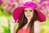 Beautiful young brunette woman on the meadow with white flowers on a warm summer day — Stock Photo