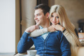 Portrait of happy young couple embracing each other and drinking coffee in a cafe — Stock Photo