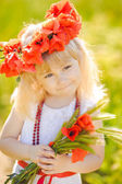 Cute child girl in poppy field — Stock Photo