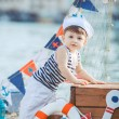 Cute little boy sitting on the floor on pier outdoor, a marine style. Little sailor — Stock Photo #38024433
