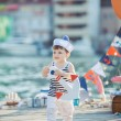 Cute little boy sitting on the floor on pier outdoor, a marine style. Little sailor — Stock Photo #38024435