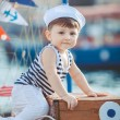 Cute little boy sitting on the floor on pier outdoor, a marine style. Little sailor — Stock Photo #38024441