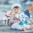 Cute little boy sitting on the floor on pier outdoor, a marine style. Little sailor — Stock Photo