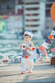 Cute little boy sitting on the floor on pier outdoor, a marine style. Little sailor — Photo