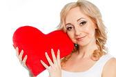 Mujer embarazada hermosa con almohada de corazón rojo en sus manos aisladas sobre fondo blanco — Foto de Stock