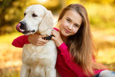 Portrait of Young girl sitting on the ground with her dog retriever in autumn scene — Photo
