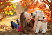 Portrait of Young girl sitting on the ground with her dog retriever in autumn scene — Stock Photo