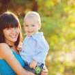 Portrait of beautiful happy smiling mother with baby outdoor — Stock Photo