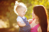 Young mother with child outside on a summer day — Stock Photo