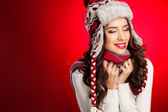 Portrait of girl in winter clothes with bright make-up on a red background — Stock Photo