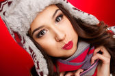 Portrait of girl in winter clothes with bright make-up on a red background — Stok fotoğraf