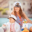 Portrait of a mother with her son playing on the jetty by the sea in the city, still life photo — Stock Photo