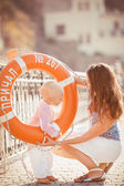 Portrait of a mother with her son playing on the jetty by the sea in the city, still life photo — ストック写真