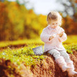 Little toddler girl sitting in green summer park — Stock Photo