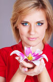 Young beautiful woman with pink flower. studio portrait — Stok fotoğraf